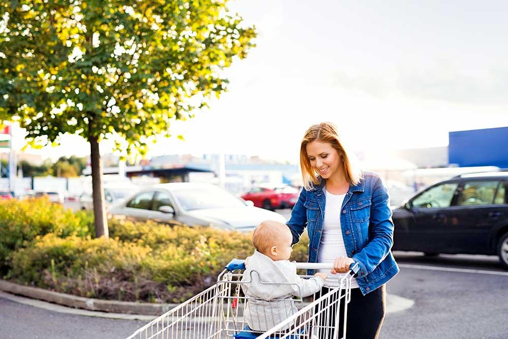 Frau mit Kleinkind am Supermarktparkplatz